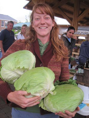Kim holding some impressive cabbages at market!